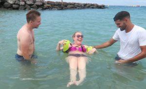 Manon in de zee met haar vriend en een begeleider.