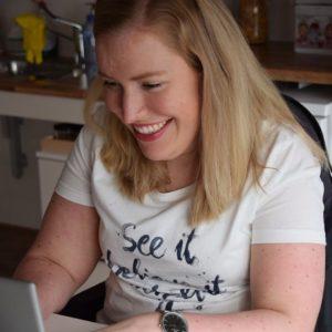 Manon achter haar laptop met een lach op haar gezicht.
