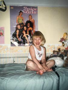 Een lachende zesjarige Manon op haar hoog-laag-bed met een poster van de Spice Girls op de achtergrond.
