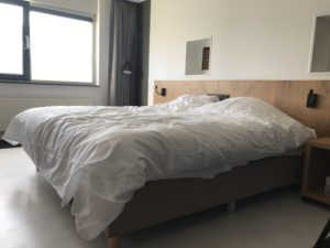 Het bed van de aangepaste hotelkamer in Golden Tulip Keyser Breda Centre.
