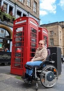 Manon in haar rolstoel voor een typisch Britse telefooncel.