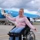 Manon lachend in de EasyTravelseat in haar rolstoel voor het vliegtuig.