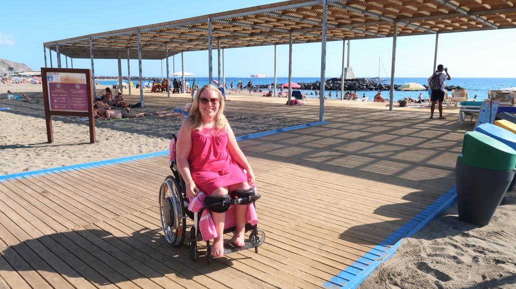 Manon in haar rolstoel op het toegankelijke strand van Playa de Las Vistas op Tenerife.